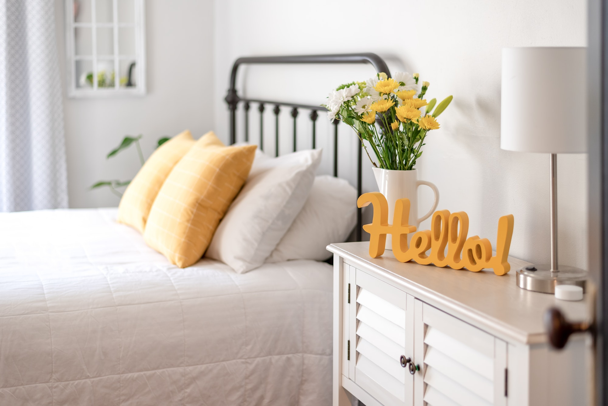 cheerful-hello-sign-and-fresh-flowers-in-a-clean-and-bright-bedroom.jpg